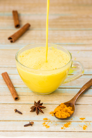 Golden turmeric milk pouring into a cup. Healthy and aromatic detox beverage.