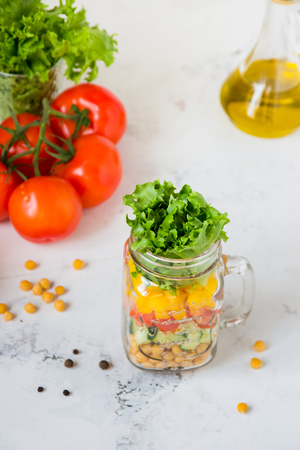Salad in a jar. Homemade healthy salad from chickpea, tomato, yellow paprika, cucumber and green lettuce.