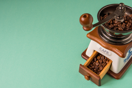 Coffee beans in a hand-held coffee grinder on a tender green background.