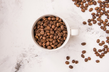 Coffee beans in a cup on a white table. Stock Photo