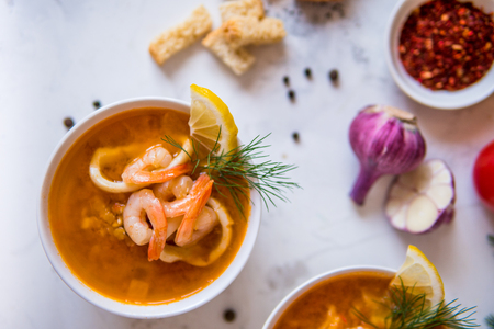Lentil soup with seafood. Red soup with shrimps and squid top view.