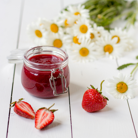 Strawberry jam in a glass jar on a table with chamomiles.