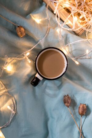 Coffee cup and garland on a bed. Atmospheric swedish hygge style. Cozy winter or autumn day