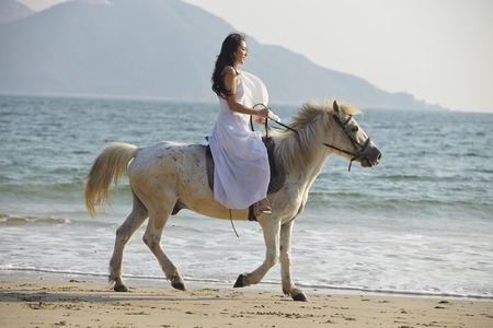 east riding: a Chinese young woman riding horse on beach