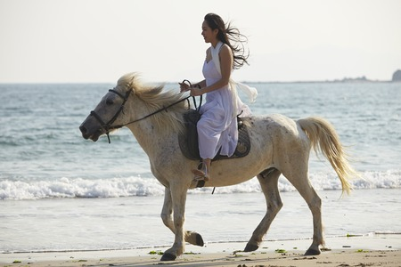 east riding: a Chinese woman riding horse on beach