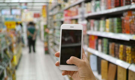 retail shopping: a shopper using mobile phone in supermarket Stock Photo