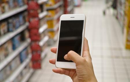 a shopper using mobile phone in supermarket Standard-Bild