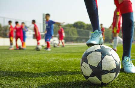 uniforme de futbol: grupo de niños asiáticos jugando al fútbol en la mañana