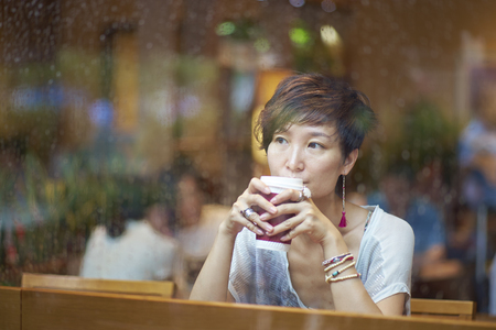 a chinese woman taking coffee break behind window