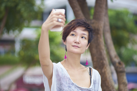 pics: young asian woman taking pics of herself in plaza
