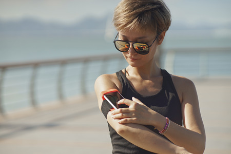 woman stop: young Asian woman stop to use mobile phone during jogging Stock Photo