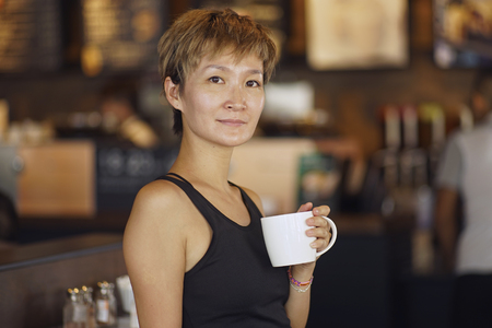 beauty shop: young beauty smiling and holding mug in coffee shop