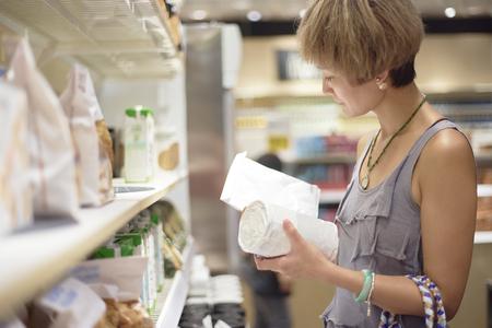 vrouw de controle op voedsel exp datum in supermarkt