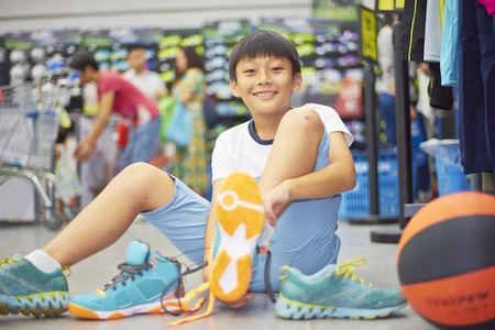 singaporean: boy sitting on ground trying sports shoes