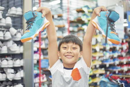 boy holding chosen shoes smiling at camera