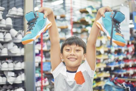 boy holding chosen shoes smiling at camera