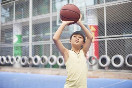 アジアの少年のバスケット ボール コートでの撮影の練習