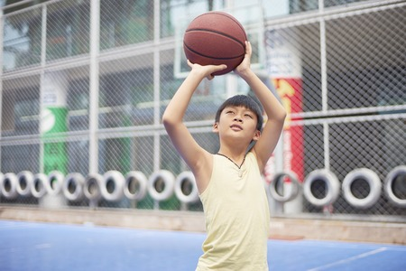 Asian boy practicing shooting at basketball court