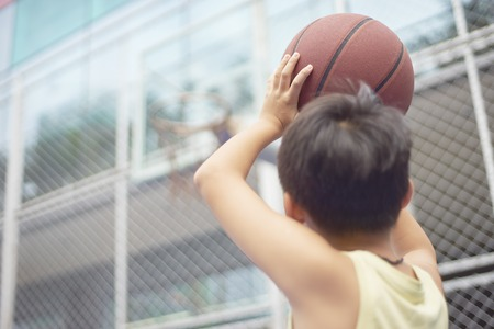 Asian boy preparing for basketball shooting at playground