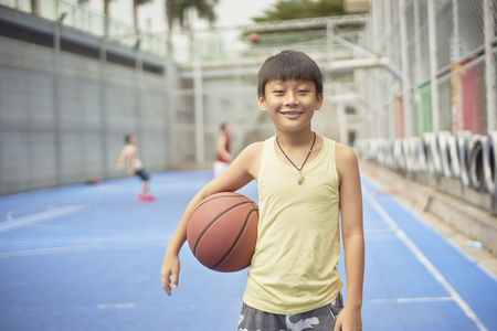 Asian boy standing at basketball court smiling