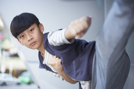 portrait of cool Asian kid playing marshal arts outdoors Stock Photo