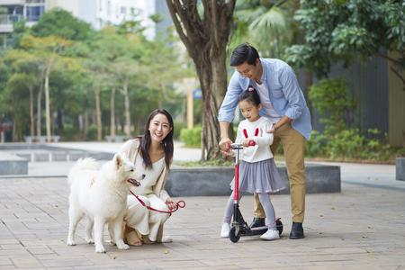 庭で犬を散歩しながらスクーターを遊ぶアジアの両親&娘 写真素材