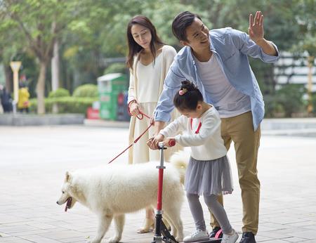 庭で犬を散歩しながらスクーターを再生するアジアの両親&娘と挨拶隣人