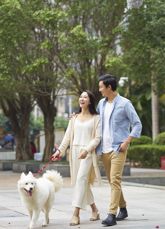 Asian couple laughing while walking dog outdoor in garden Standard-Bild