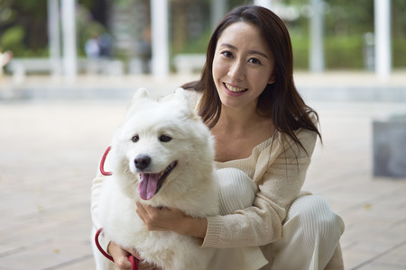 Asian beauty embracing her dog smiling at camera outdoor in garden Stock Photo - 92273821