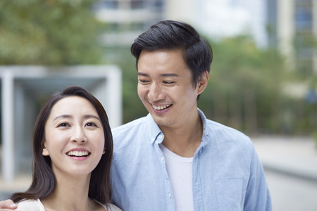 Portrait of young Chinese couple standing smiling outdoor
