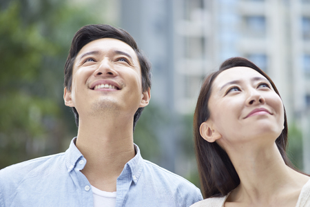 Portrait of young Chinese couple standing smiling outdoor in garden