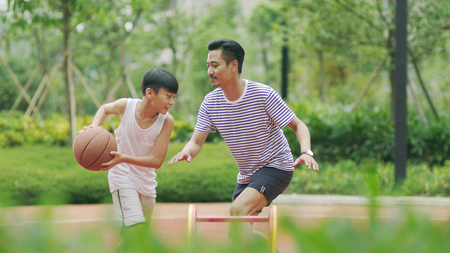 Chinese father playing basketball with son