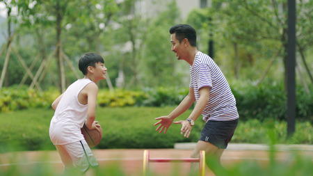 Asian father playing basketball with son