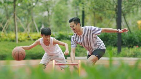 Aziatisch vader speelbasketbal met zoon Stockfoto