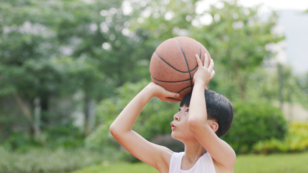 teenage Asian boy playing basketball outdoors preparing for shooting