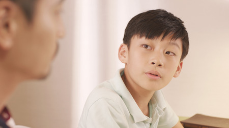 Asian father talking & counseling his frustrated teenage boy at home Standard-Bild