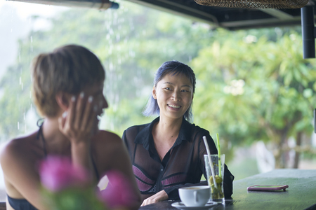 portrait of 2 asian women chatting, drinking & smiling at beach bar in summer 스톡 콘텐츠