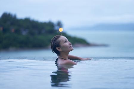 Asian beauty enjoying vacation in infinity pool at dawn, ko samui, thailand