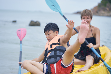 Asian mother and son playing kayaking on the sea during vacation when kid falling balance