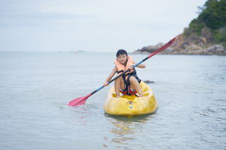 Asian kid kayaking alone on the sea wearing life vest