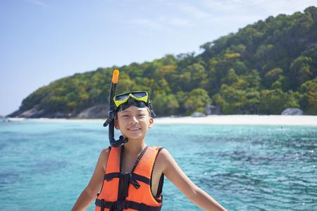 Glücklicher asiatischer Junge, der Schnorchel trägt und sich auf das Schwimmen in Phuket, Thailand vorbereitet Standard-Bild