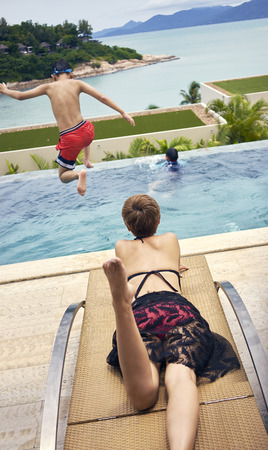 Rear view of Asian woman lying for sunbathing on deck chair while kid jumping into pool
