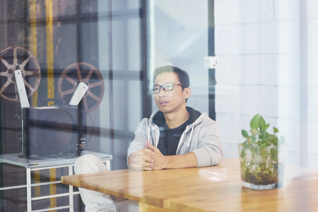 Portrait of Asian businessman looking outside and contemplating while sitting in office