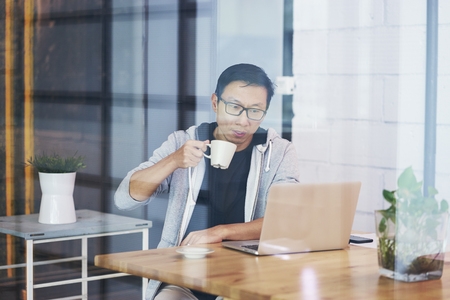 Portrait of Asian businessman drinking coffee while working on laptop in office Stock fotó