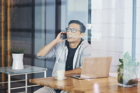 Portrait of Asian businessman making phone call while working in office Standard-Bild - 118768825