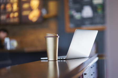 cup and laptop on table inside a coffee shop Stock fotó
