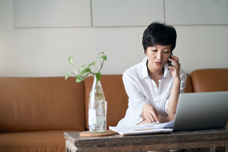Asian self employed woman talking on smartphone while working on laptop at home Standard-Bild - 123616276