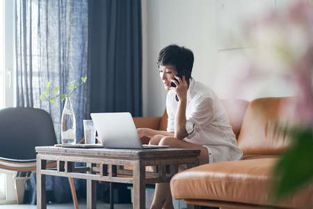Asian self employed woman talking on smartphone while working on laptop at home Standard-Bild - 123616277