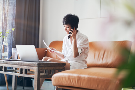 Asian self employed woman talking on smartphone while working on laptop at home Stock Photo