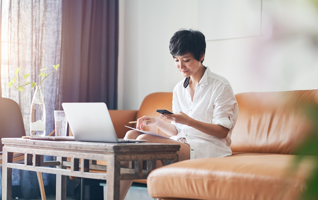 Asian self employed woman sitting on couch using smartphone while working on laptop at home